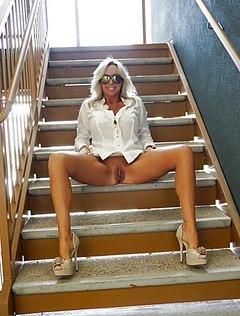 Женщина без лифчика и трусиков позирует дома
