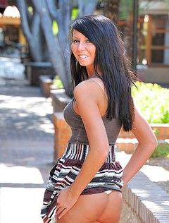 Темноволосая кошечка весело подняла юбку на улице