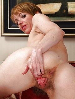 Женщина с короткой стрижкой показывает небритую пизду