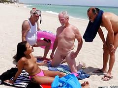 Самцы трогают руками на пляже голенькую