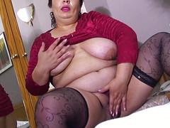 Толстуха массирует на кровати половую щелку