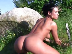 Девушка ласкает на природе сиськи и вульву