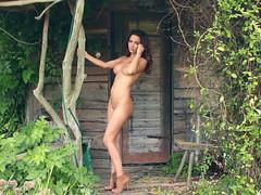 Брюнетка позирует в голом виде около деревенского дома
